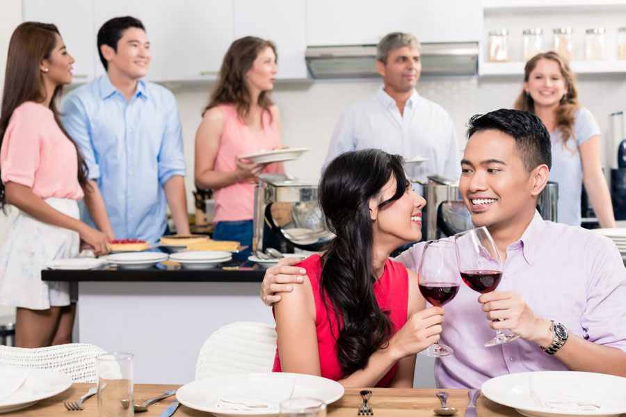 Friends celebrate in a kitchen.