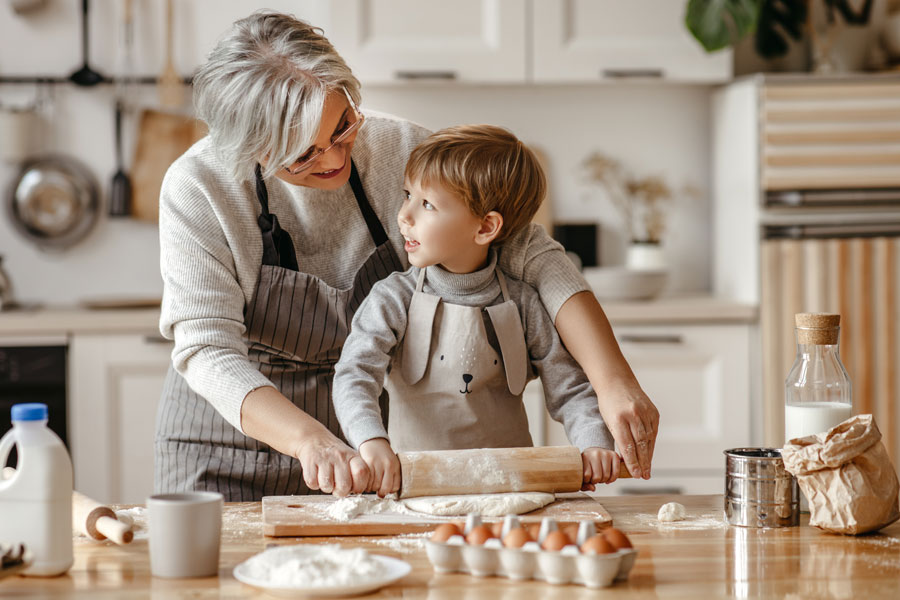Grandma and grandson baking in a kitchen.