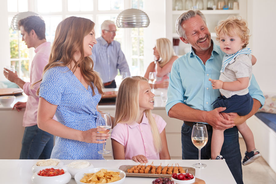 Multi-generational family and friends gathering in a kitchen.